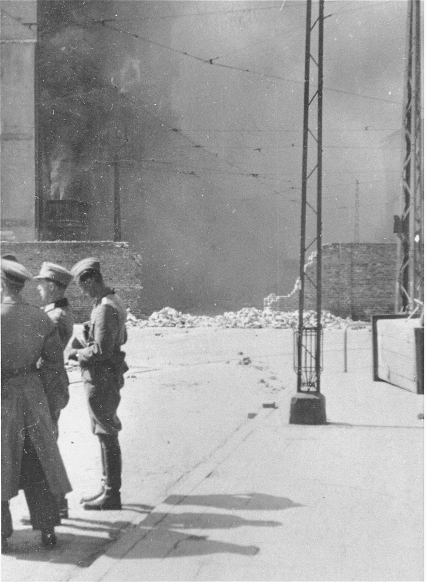 German personnel discuss matters as an apartment building razed by the SS burns during the suppression of the Warsaw ghetto uprising.