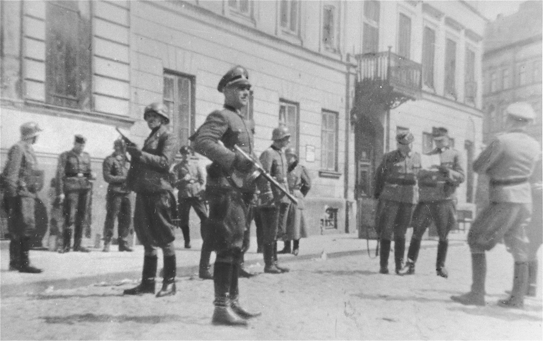 SS and police officers look on as SS Major General Juergen Stroop discusses razing the houses on Niska and Muranowska Streets with Kaleschke, his police adjutant.