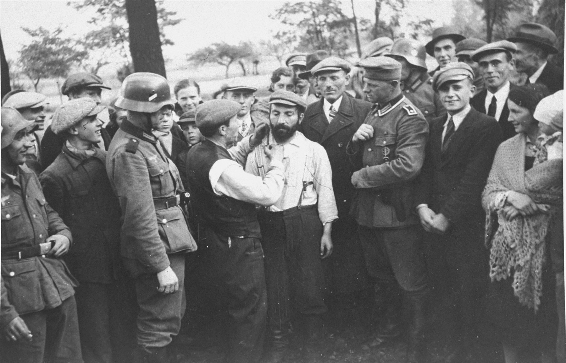 A group of German soldiers and civilians look on as a Jewish man is forced to cut the beard of another in Tomaszow Mazowiecki.