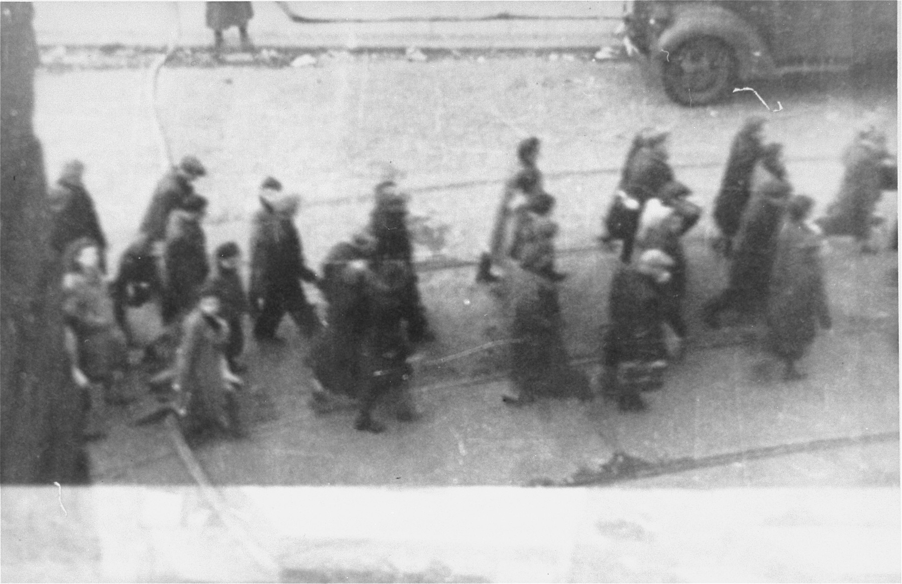 Jews captured by the SS during the suppression of the Warsaw ghetto uprising march past the St. Zofia hospital down Nowolipie Street towards the Umschlagplatz for deportation.