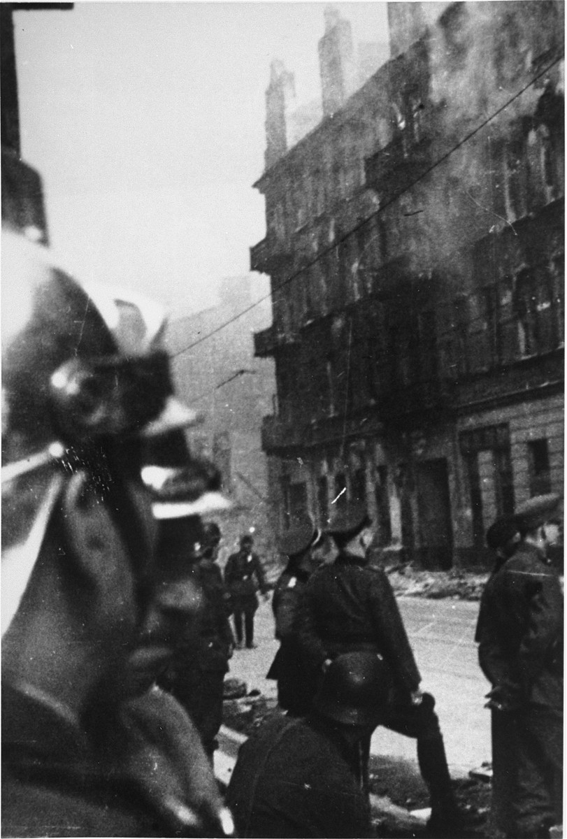 "Polish firefighters and SS officers in the Warsaw ghetto during the suppression of the uprising.    The original Polish caption reads: ""The Germans set fire to the buildings evacuated by the Jews.  From a balcony on the top floor a family of five or six people jumped to their deaths.  They didn't leave earlier as ordered and then they couldn't run away.  We didn't help them even though technically we could have."""