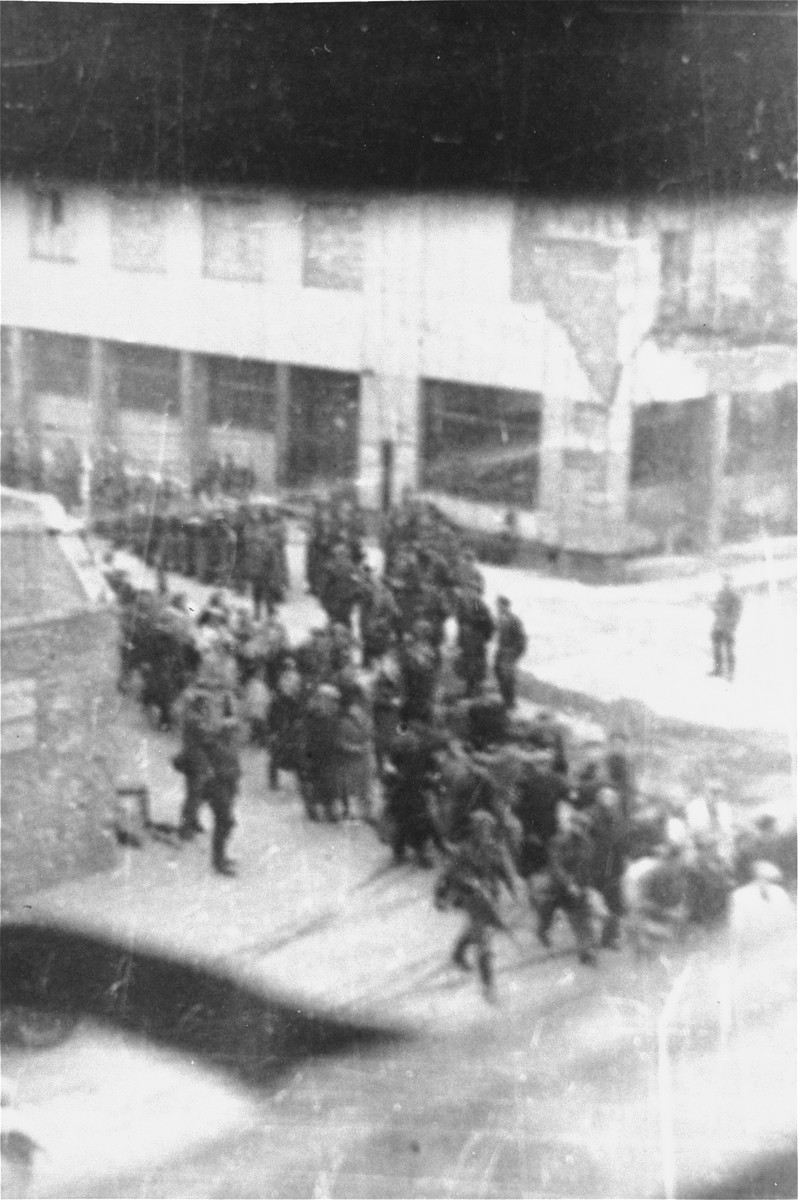 Jews captured by the SS during the suppression of the Warsaw ghetto uprising march past the St. Zofia hospital, through the intersection of Nowolipie and Zelasna Streets, towards the Umschlagplatz for deportation.