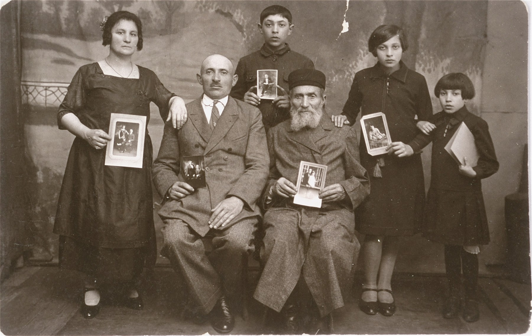 Portrait of Szultz family in Grojec, Poland, holding photographs of their children, some of whom had immigrated to the United States.   Pictured from left to right are Bintcha, Yishmael, Shaul, grandfather Szultz, Rochelle and Esther Szultz.