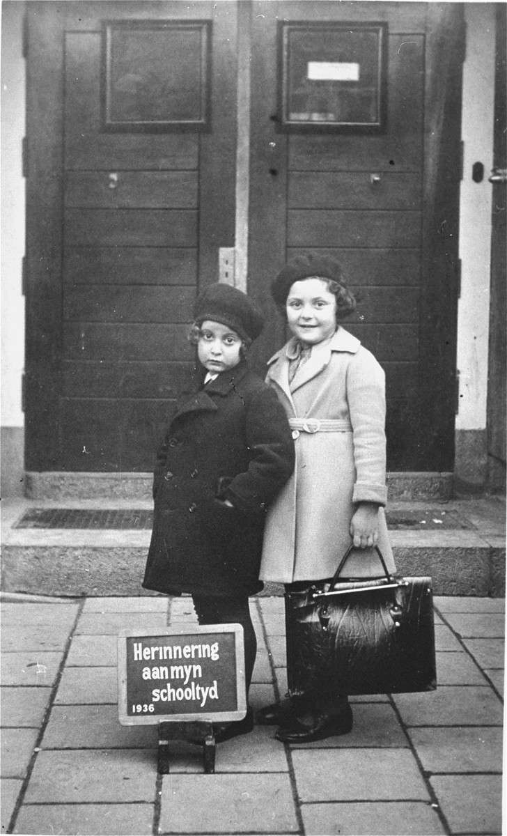 Portrait of two Jewish girls at the entrance to their school on their first day of classes.  Pictured are the donor, Hetty d'Ancona de Leeuwe (left), and her best friend, Judith Konyn.