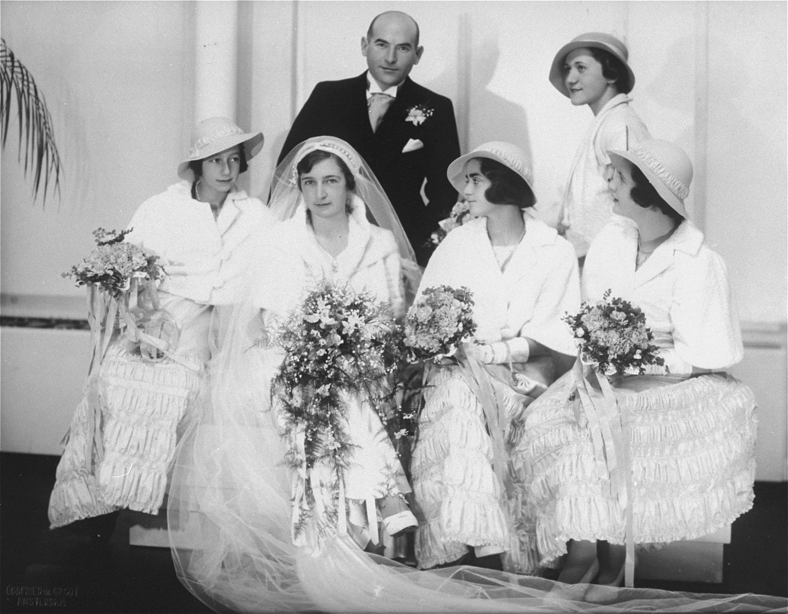 Group portrait of Hilde and Gerrit Verdoner with four bridesmaids on their wedding day.    Pictured from left to right are: Jetty Fontijn, Hilde Verdoner, Letty Stibbe, and Miepje Sluizer; standing behind them is Fanny Schoenfeld.