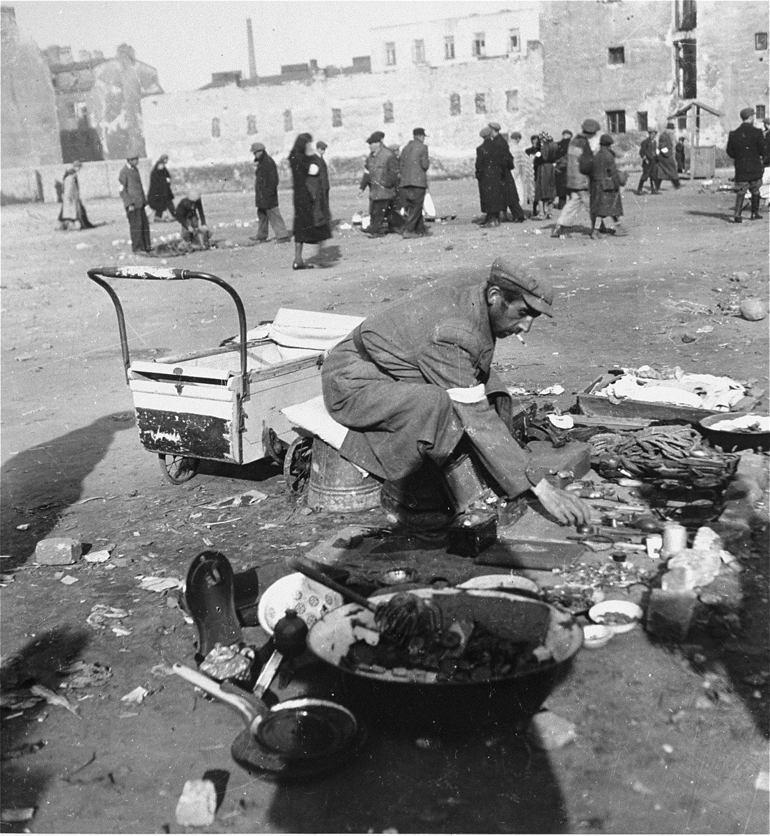 """A man offers various items for sale on a lot in the Warsaw ghetto.   Joest's original caption reads: """"This man offered [for sale] nothing anyone could need: old pans, heavy, dented bowls, an old cauldron.  However, he had to try any way he could to make money to live."""""""
