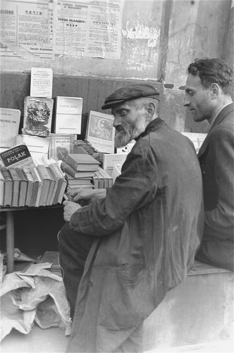 """Book vendors sit in front of a table piled with books on a street in the Warsaw ghetto.    Among the book titles for sale are: """"A Pole in Germany,"""" """"Death of a Poet,"""" """"Wilhelm II,"""" and """"Sexual Life.""""  Posted on the wall above the stand are announcements warning about typhus and lice, one of which is signed by Jewish Council chairman Adam Czerniakow."""