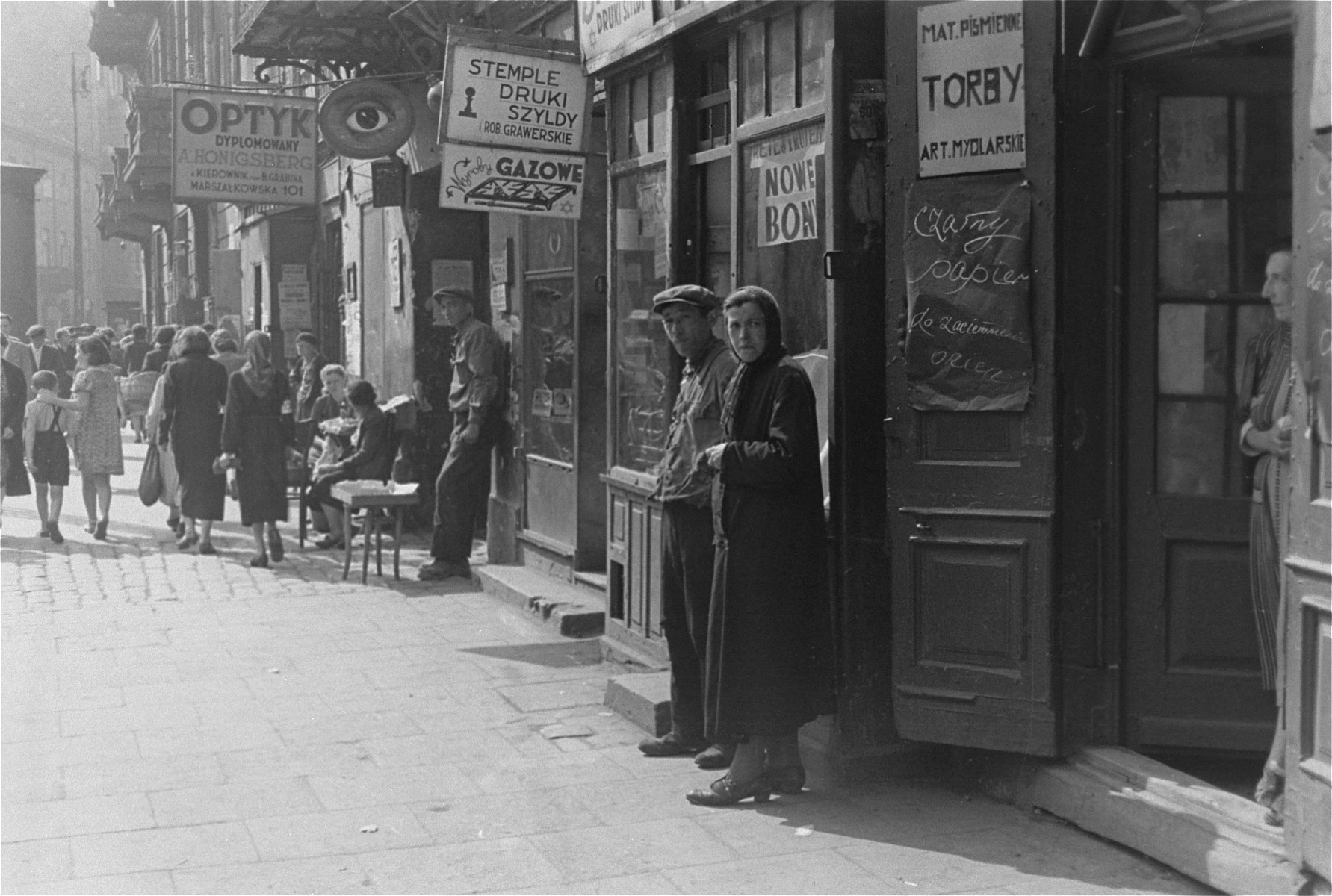 View of a commercial street in the Warsaw ghetto   The store at right sells black paper for covering windows, as well as soap and writing materials.