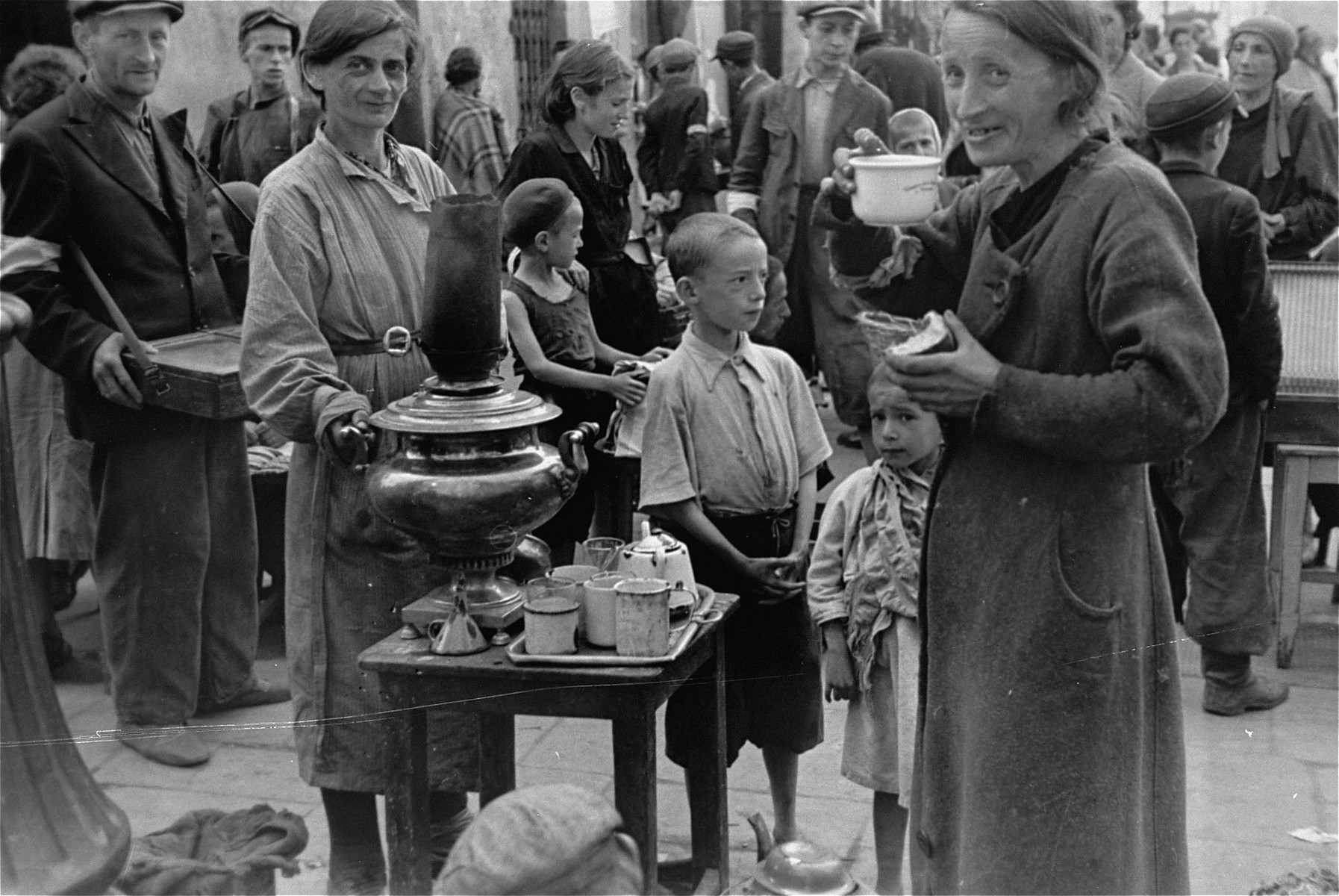 A woman drinks a cup of tea and eats a piece of bread she purchased from a vendor at an open air market in the Warsaw ghetto.