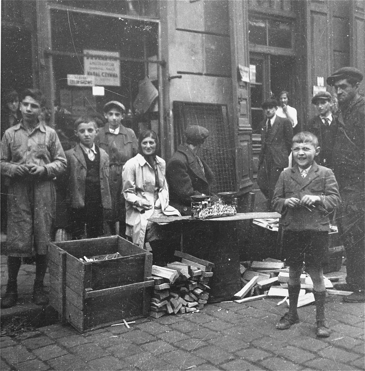 """Vendors sell blocks of wood and kindling on the street in the Warsaw ghetto.    Joest's original caption reads: """"Both of these vendors weighed pieces of wood and kindling with a kitchen scale.  Truly, with the scale!"""""""