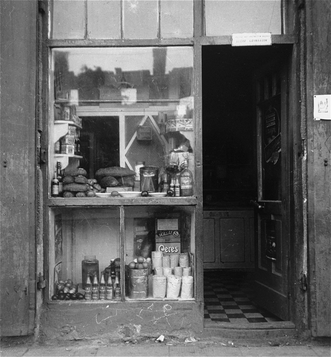"""The front of a small ghetto grocery store owned by Lejzor Grynbaum.    Joest's original caption reads: """"This was a small shop.  To me the name Grynbaum stood out.  There were onions, soda water, bread, packages of soup, and dried fruit.  I saw no one shopping there."""""""