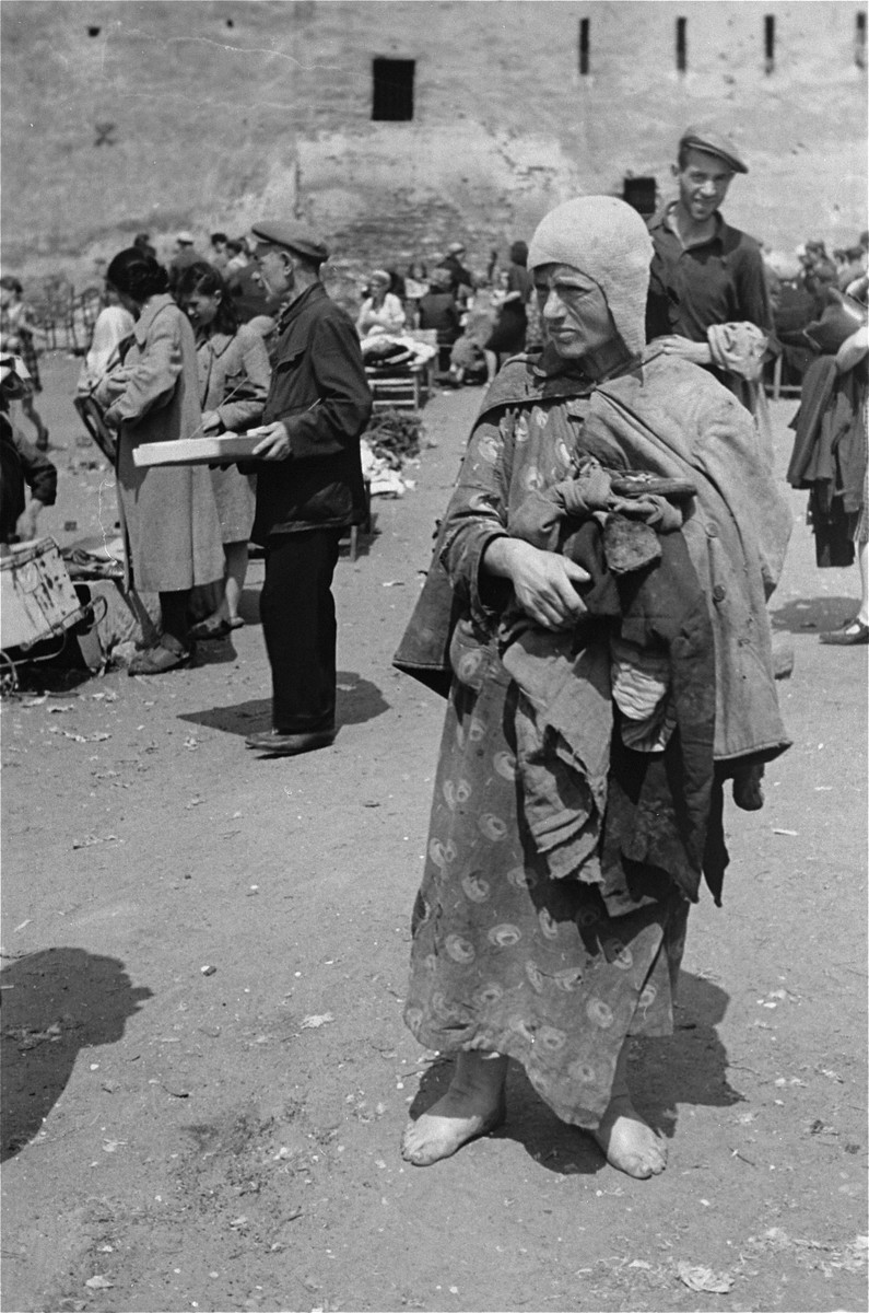 A barefoot woman at an outdoor market in the Warsaw ghetto.