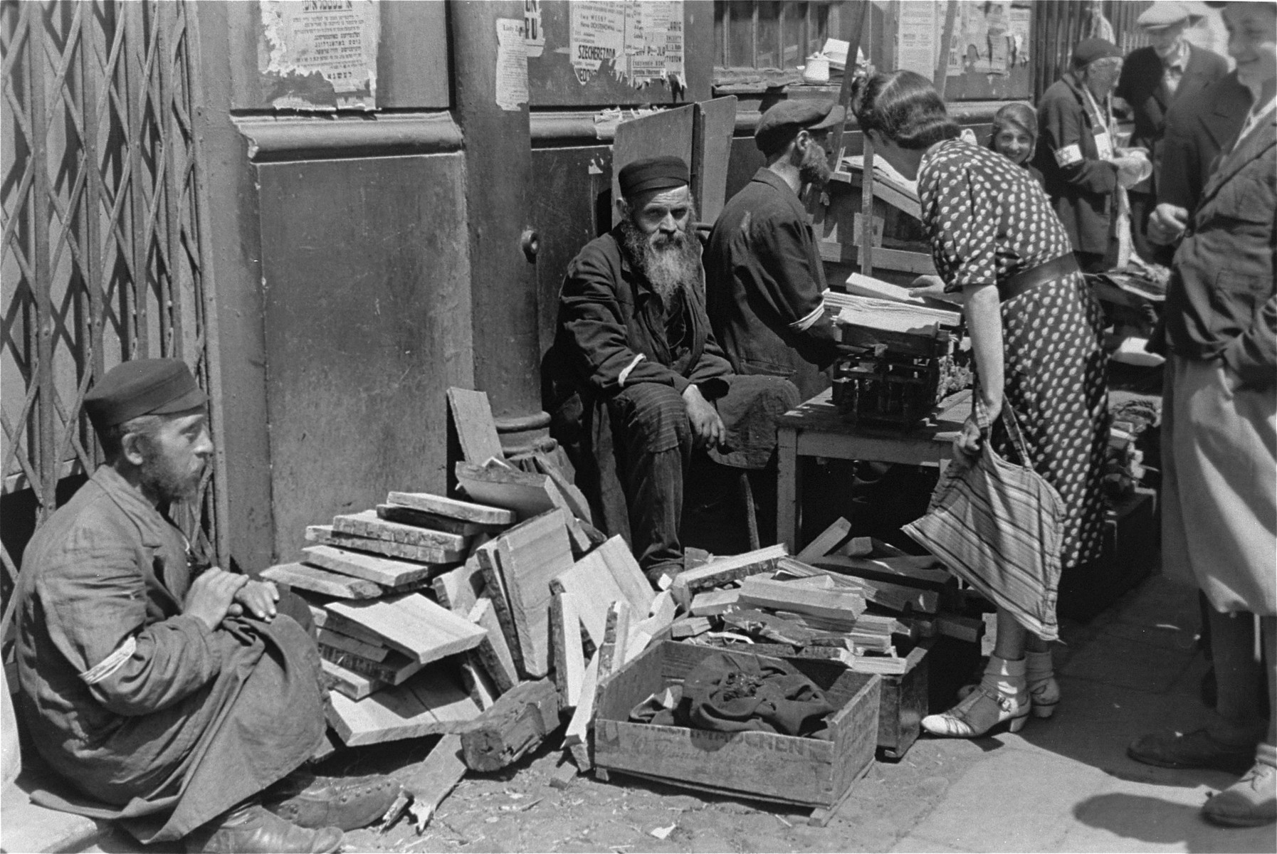 A woman purchases kindling from a street vendor in the Warsaw ghetto.
