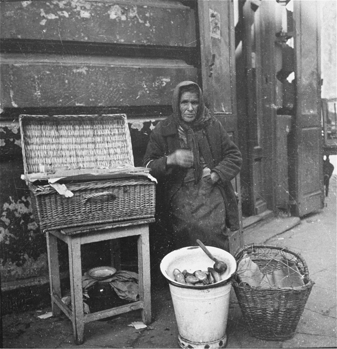 "A woman vendor on the street in the Warsaw ghetto offers pickles and food for sale.    Joest's original caption reads: ""This woman offered different food [for sale] on the street.  I do not know where it was.""  In 1987, Ahron Potschnik in Tel Aviv recognized his mother in this photograph."