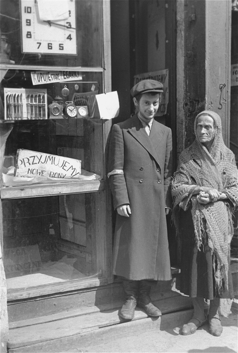 "A young man and an elderly woman stand in the doorway of a shop in the Warsaw ghetto.  The sign reads: ""We accept new coupons and buy old watches."""