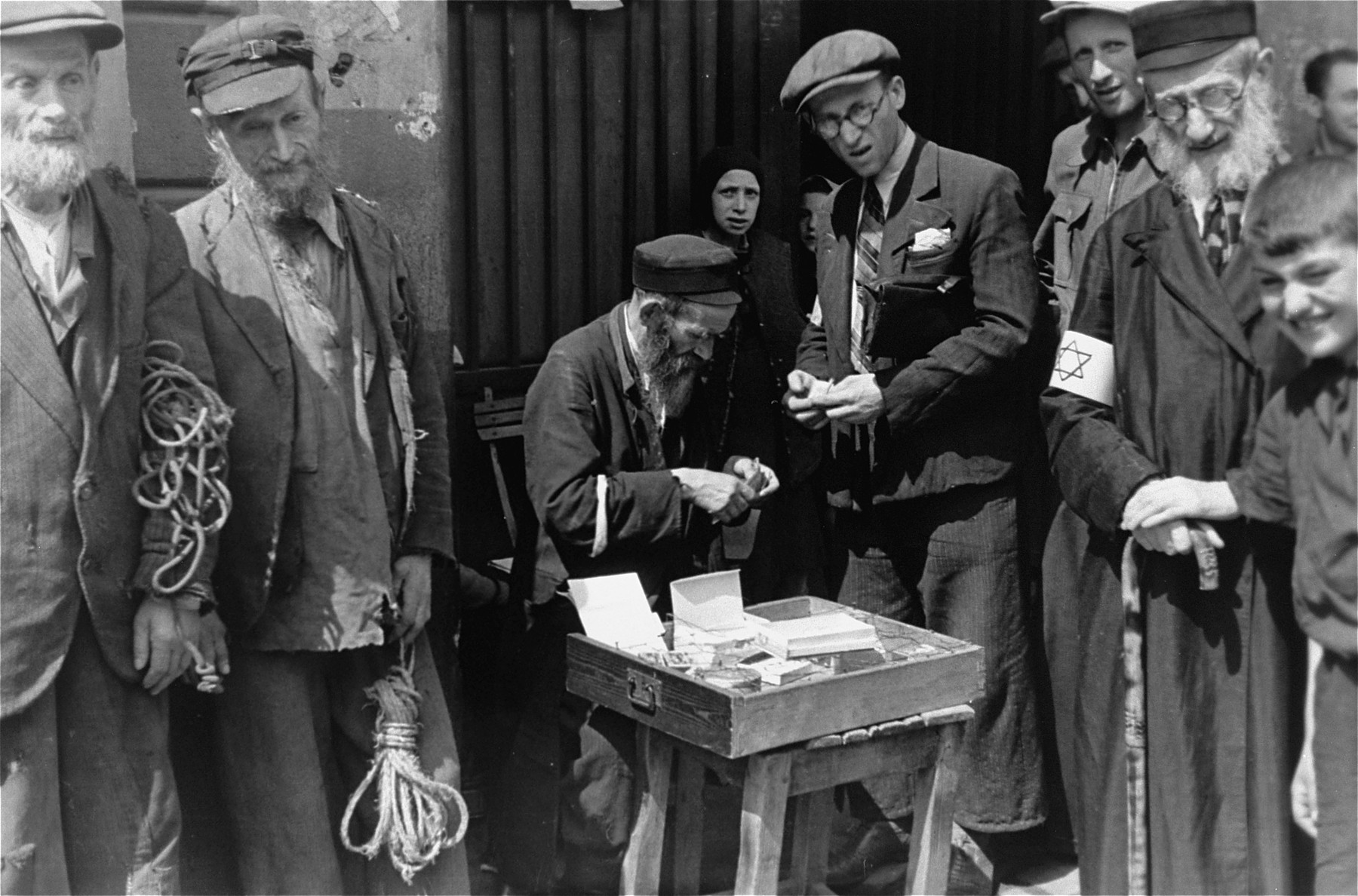 A group of people are gathered around a street vendor in the Warsaw ghetto, who is conducting business with one of them.