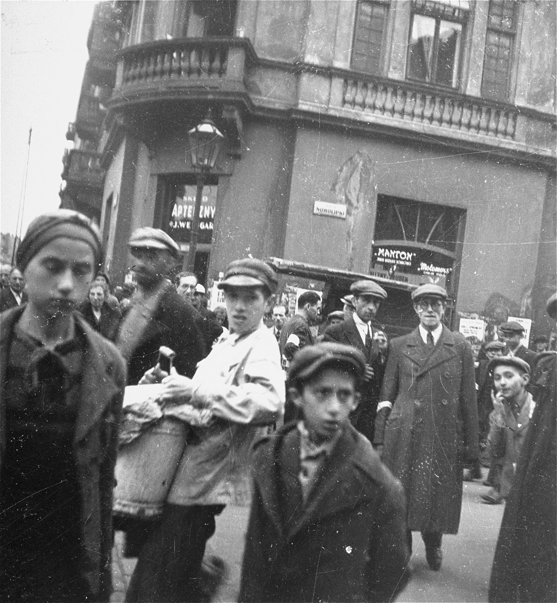 """Jews in the Warsaw ghetto on the corner of Nowolipki Street.    Joest's original caption reads: """"Although most of the people were sick, I never saw anyone go into the apothecary shop on Nowolipicki Street."""""""