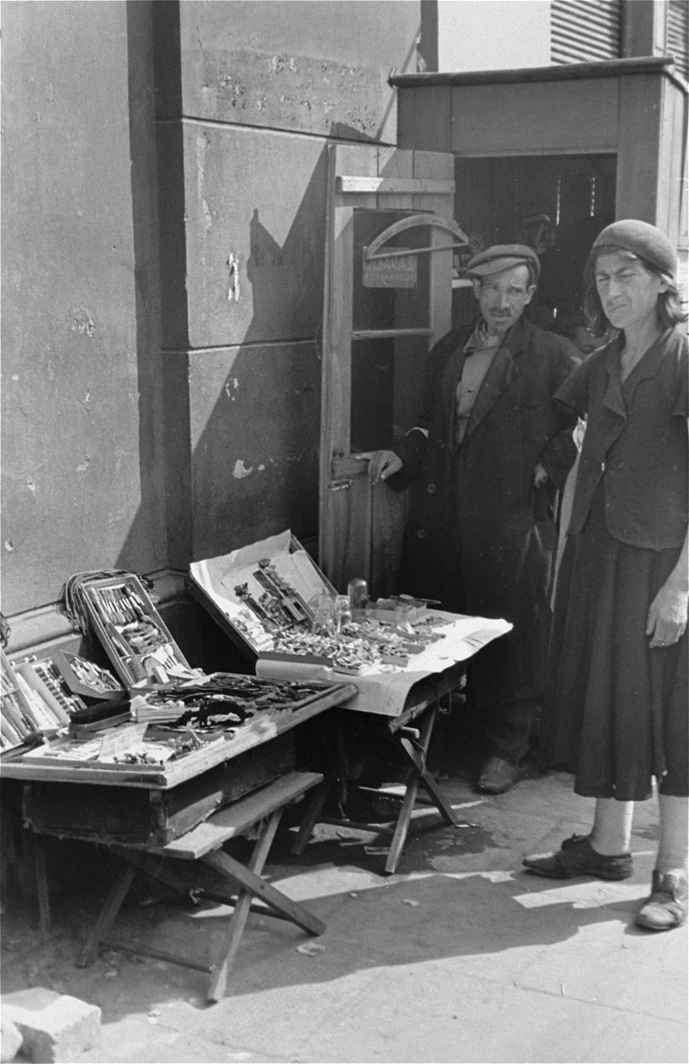 Street vendors stand next to their display tables in the Warsaw ghetto.
