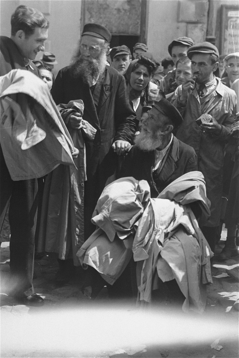 A street vendor selling overcoats haggles with a customer at an open air market in the Warsaw ghetto.