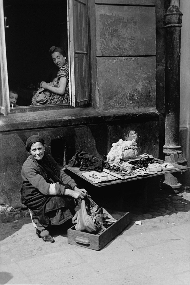A female vendor offers jewelry, used clothing, and other items for sale on the street in the Warsaw ghetto.