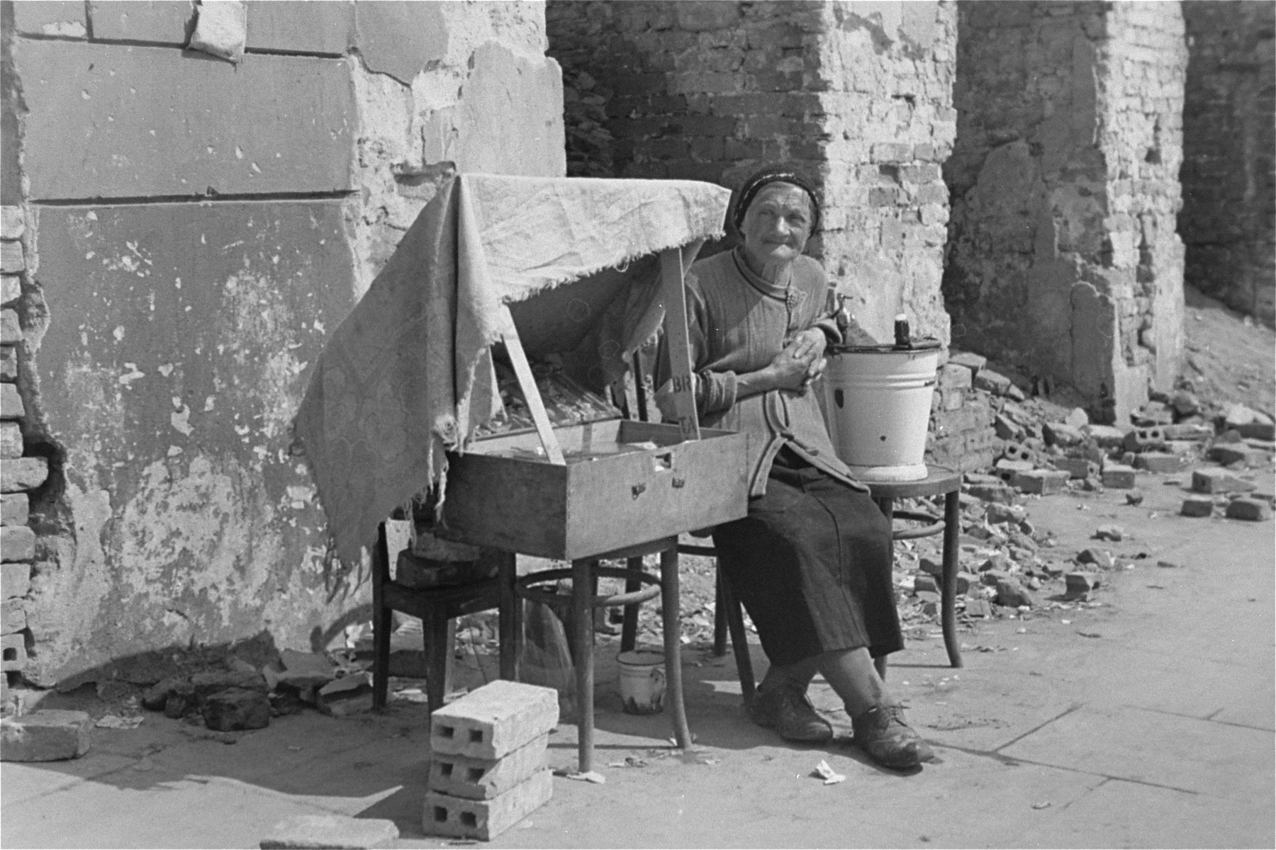 An elderly woman sits next to her makeshift vending stand amid the rubble on a street in the Warsaw ghetto.