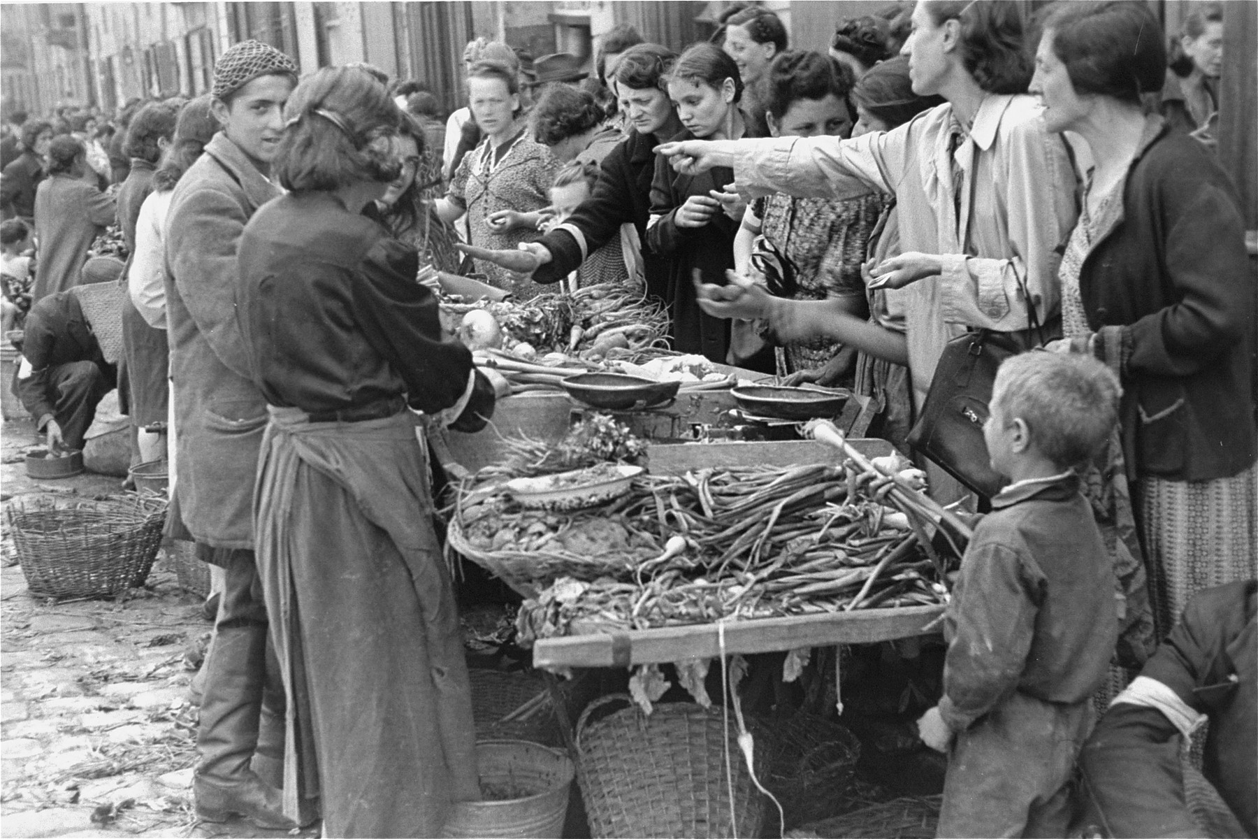 Jewish vendors sell vegetables at an open air market in the Warsaw ghetto.