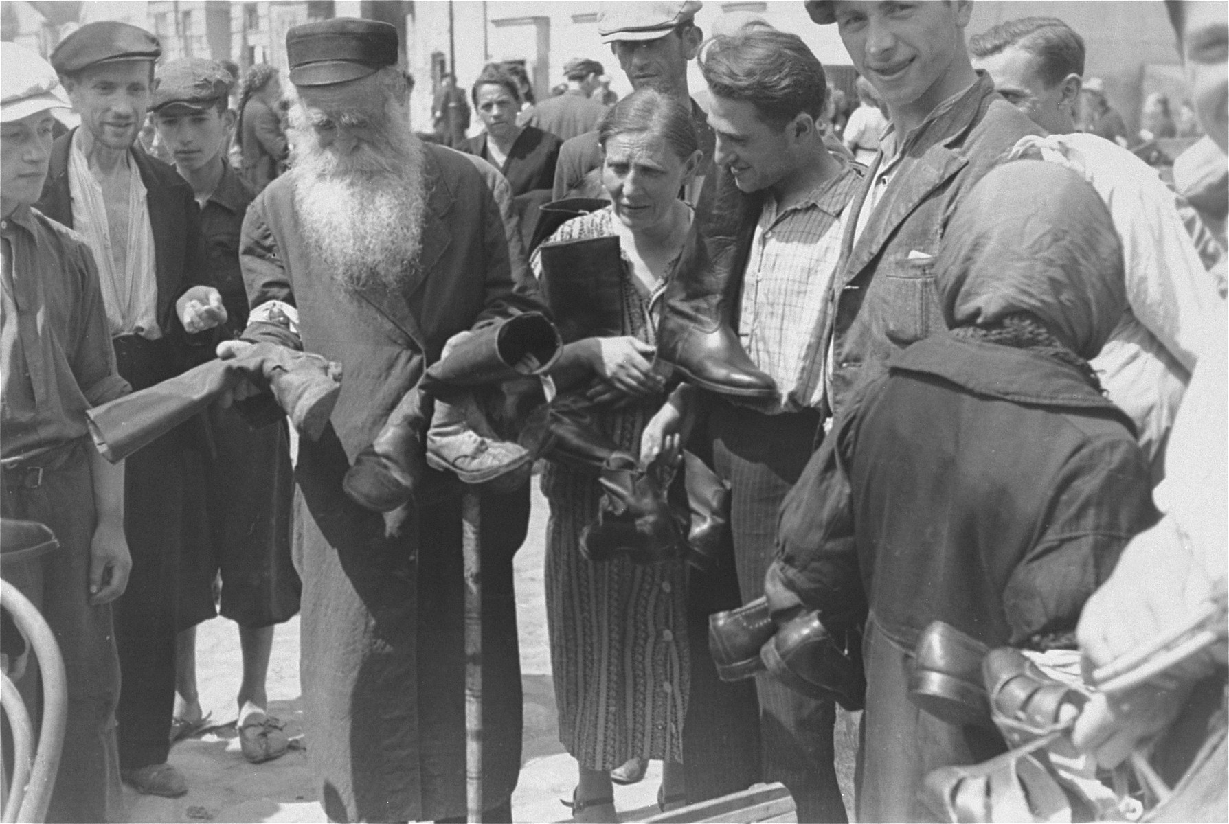 An elderly, religious Jewish vendor offers old shoes and boots for sale at an outdoor market in the Warsaw ghetto.