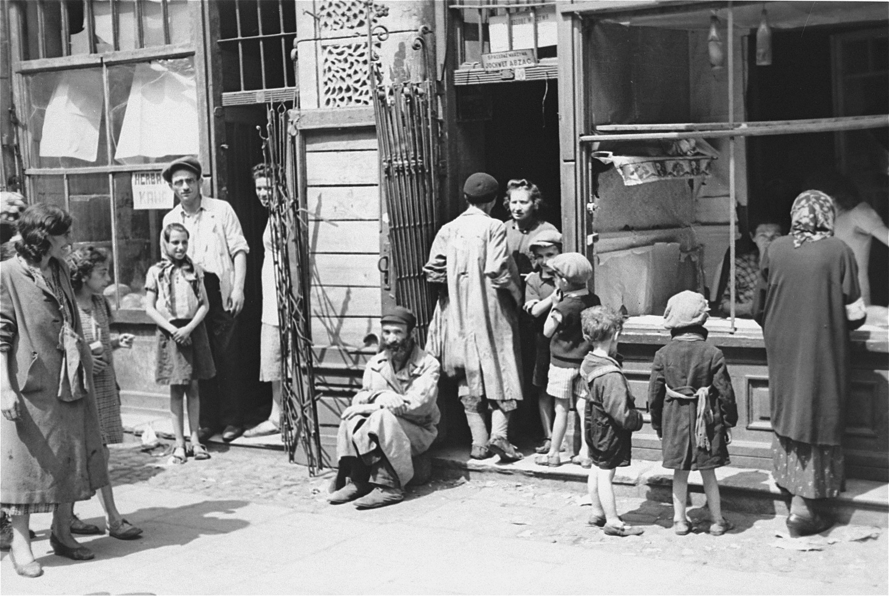 A group of Jews are gathered in front of a vegetable store owned by Jochewet Abzac in the Warsaw ghetto.