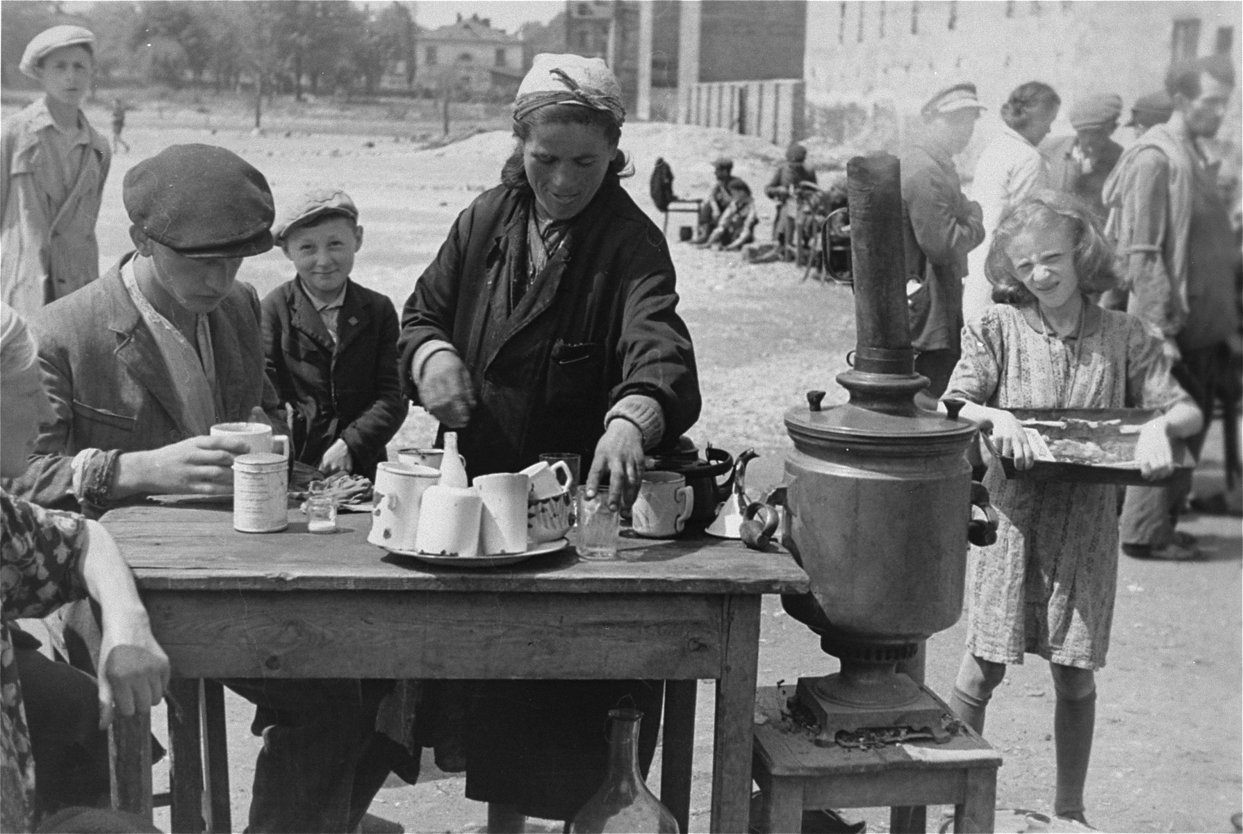Street vendors in the Warsaw ghetto offer hot tea for sale at an open air market.