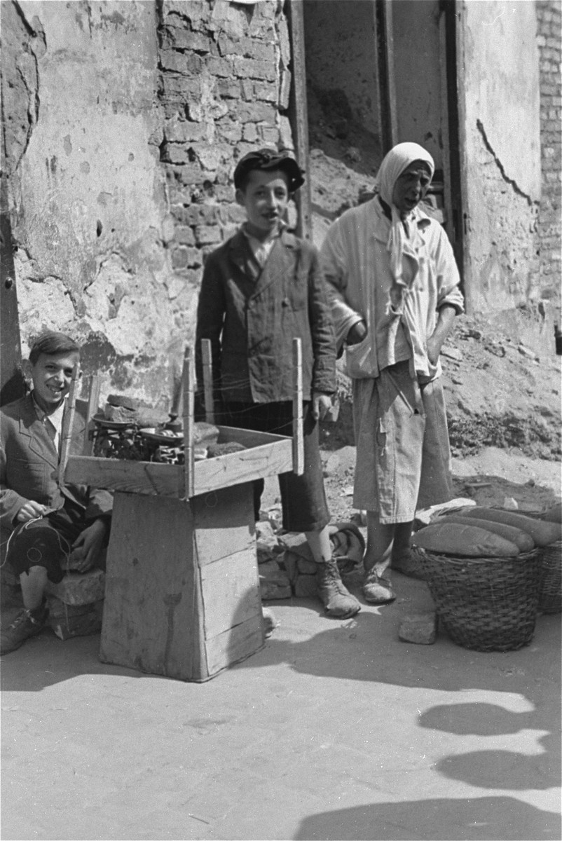 Two Jewish youth and an elderly woman sell bread on the street in the Warsaw ghetto.