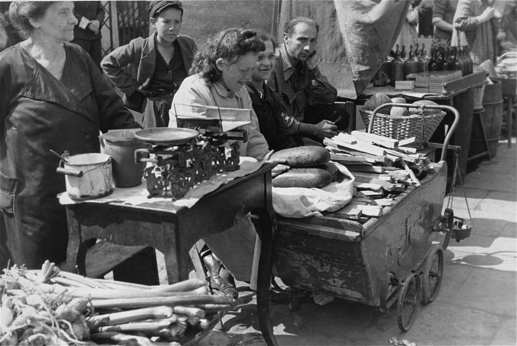 Street vendors in the Warsaw ghetto offer bread and kindling for sale.