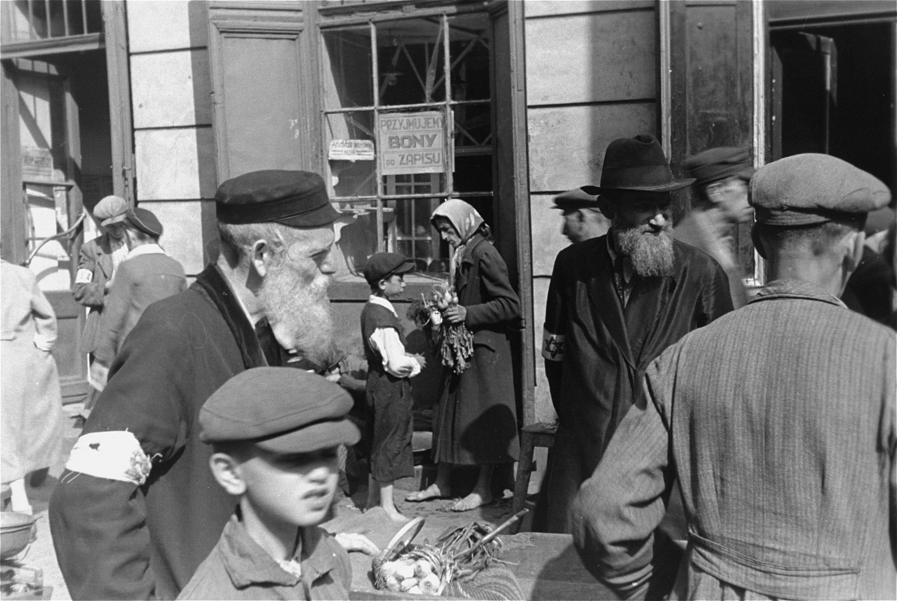 Ghetto residents make purchases from street vendors in the Warsaw ghetto.