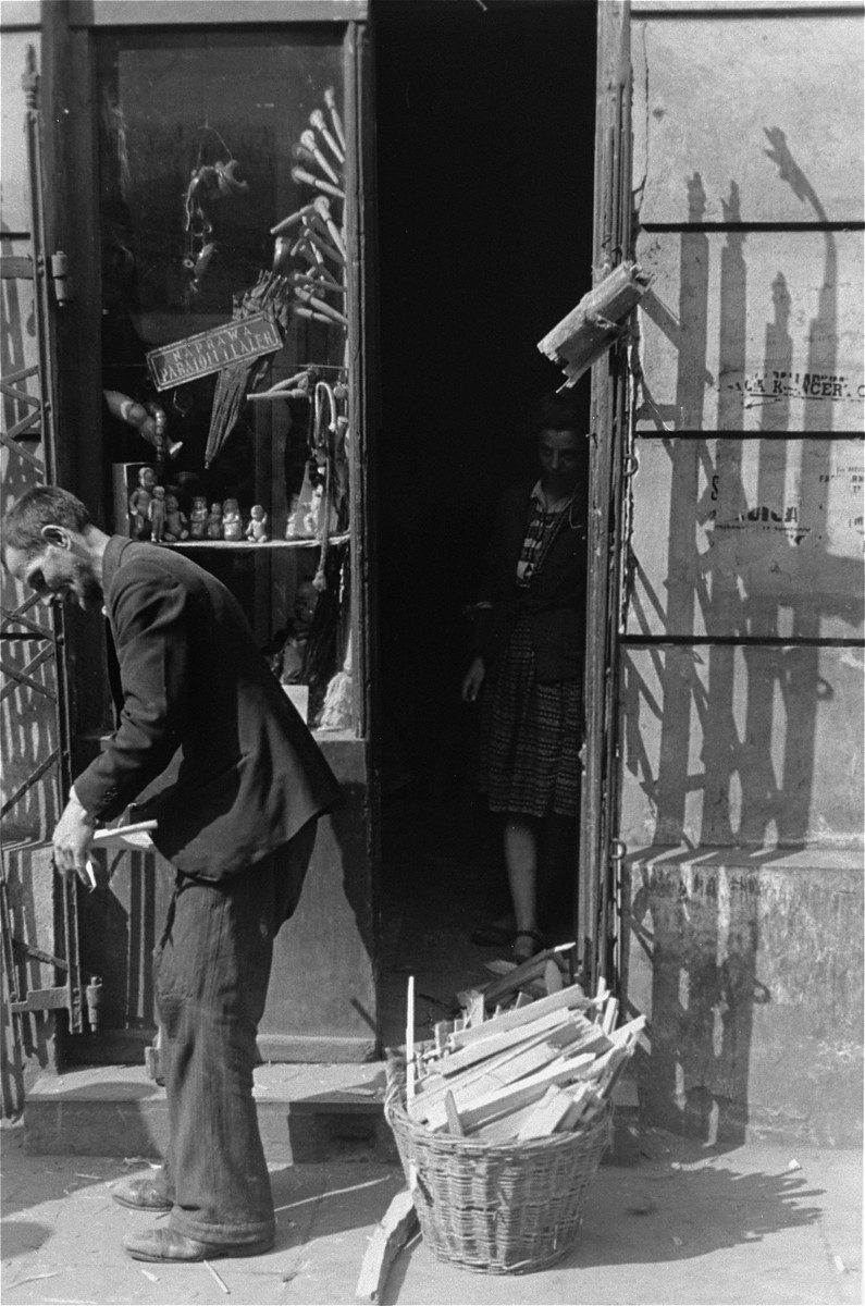 A vendor selling kindling stands in front of a store that specializes in the repair of umbrellas and dolls.