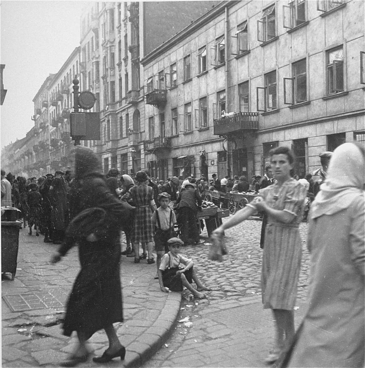 "Vendors in the Warsaw ghetto hawk their goods to passing customers at the market on Krochmalna Street.  Joest's original caption reads: ""The Krochmalna street was a mob [of people]."""
