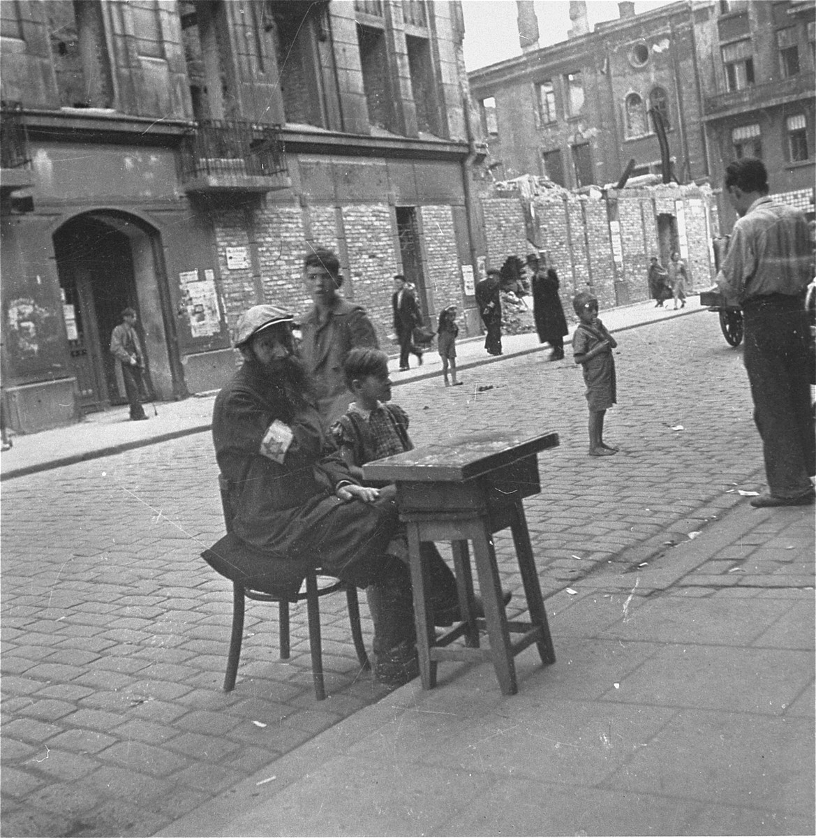 """A vendor on the street in the Warsaw ghetto.    Joest's original caption reads: """"This man was selling something.  I don't know more [about it], was it cigarettes?  The fact that small boy was barefoot on this September day again stood out to me."""""""