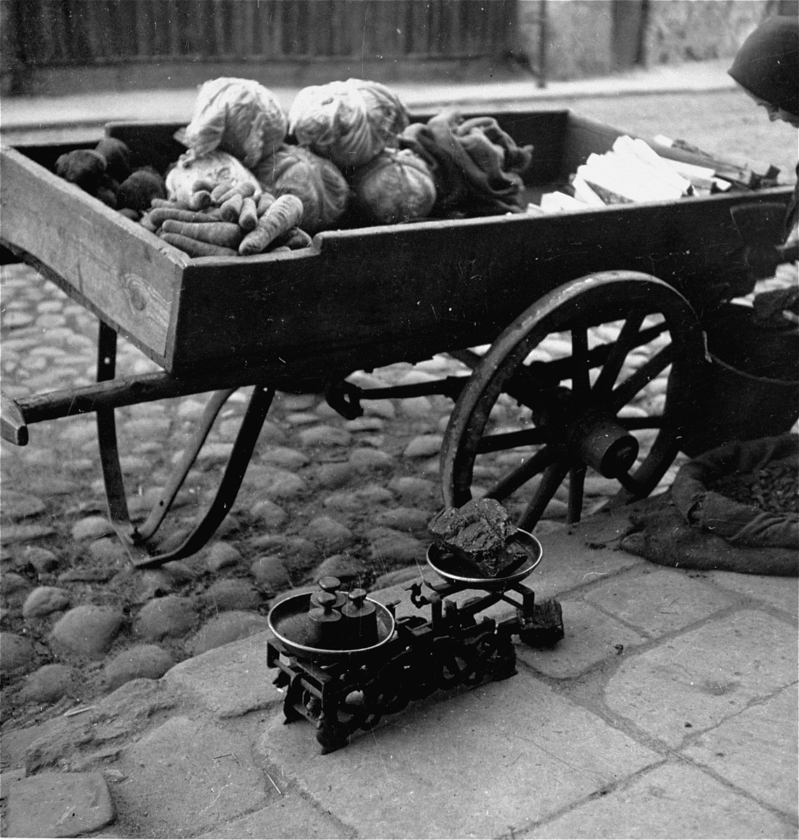 """A woman in the Warsaw ghetto offering vegetables and kindling for sale on the street hacks apart lumps of coal with a hatchet.    Joest's original caption reads: """"This woman had already weighed out a piece of coal on a scale.  She also had roots and coal on her vending cart."""""""