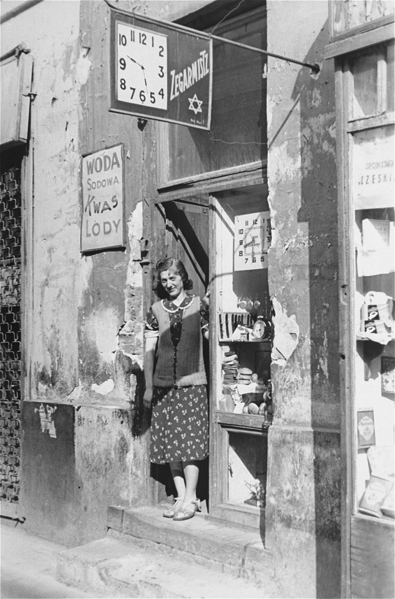 A woman stands in the doorway of a watchmaker's shop in the Warsaw ghetto.