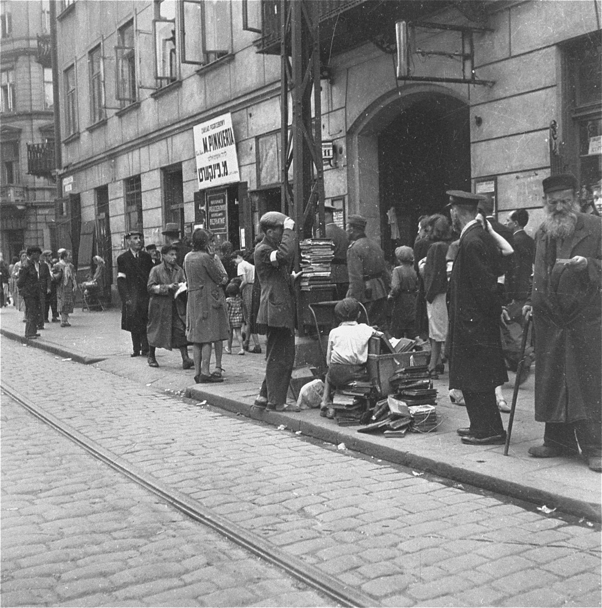 "A vendor sells used books on Nowolipiki Street near the undertaker's business of Mordechai Pinkiert.    Joest's original caption reads: ""This was Nowolipiki Street, with the office of an undertaker.  I did not notice the name Mordechai Pinkiert at that time."""