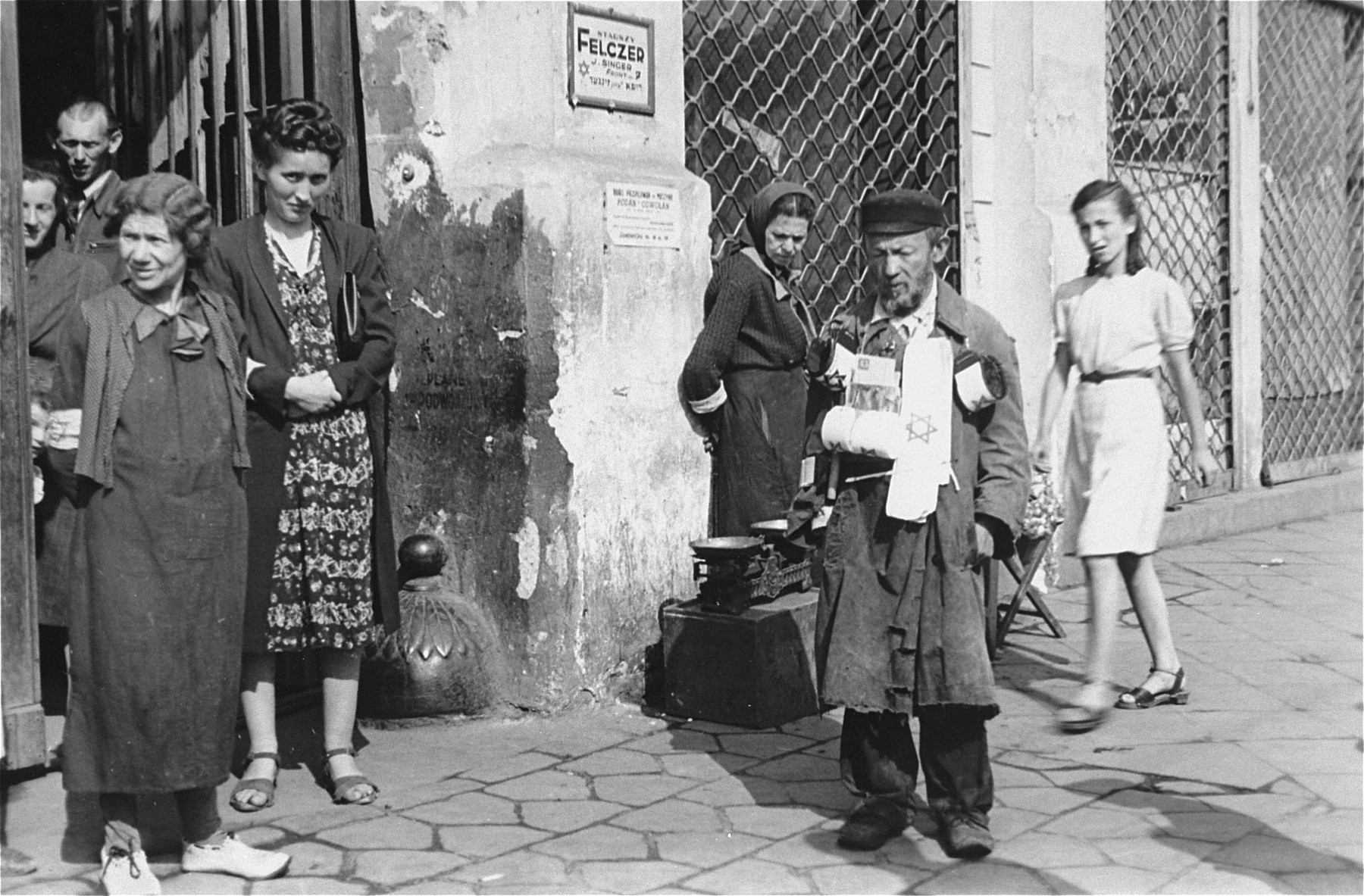 An elderly man sells Jewish armbands at the entrance to a building in the Warsaw ghetto.