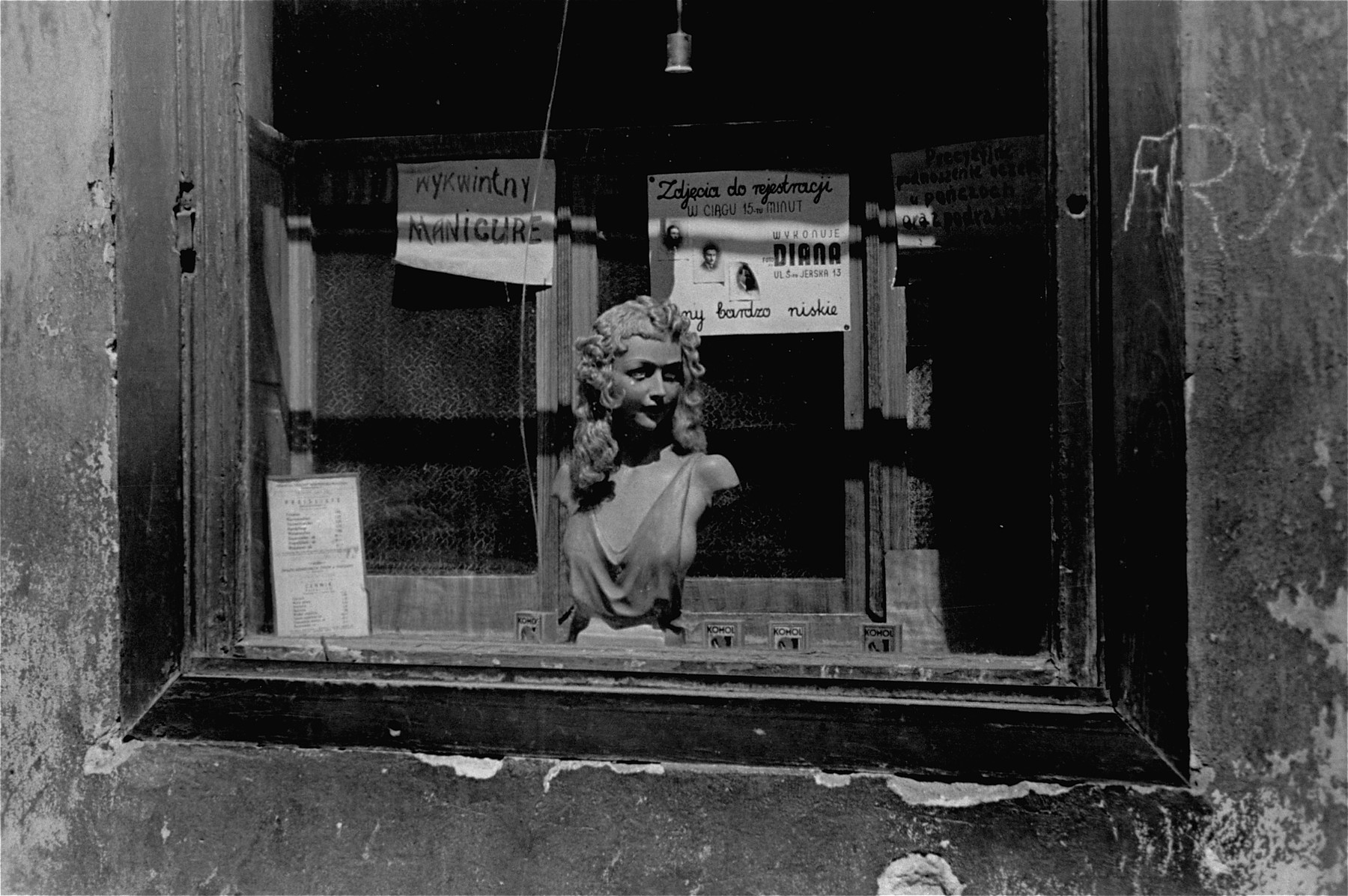"A shop window in the Warsaw ghetto advertising different services, including stocking repair, passport photos and manicures.  The chalk sign on the wall reads ""barbershop."""