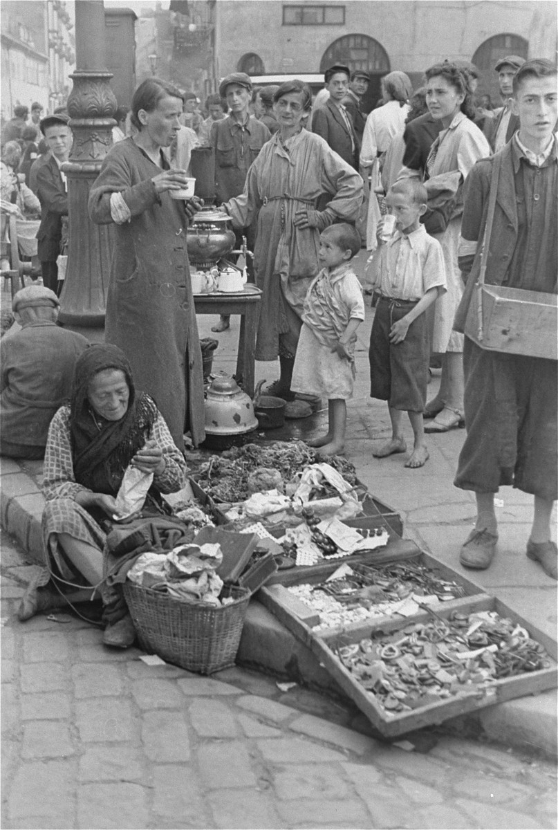 Female vendors sell goods and beverages at an outdoor market in the Warsaw ghetto.