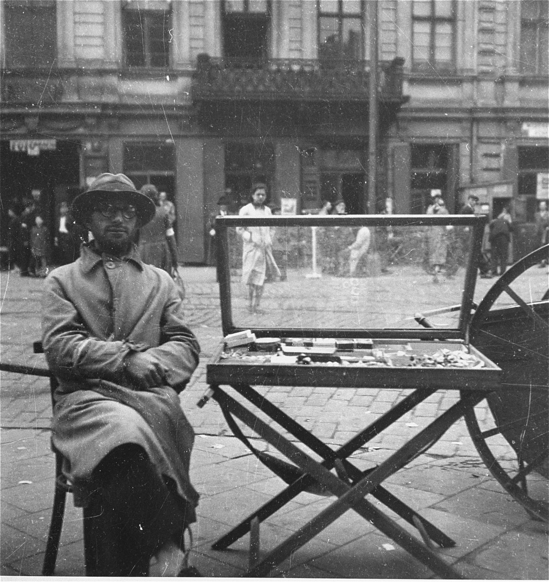 """A cigarette and match vendor on Zelazna Street in the Warsaw ghetto.    Joest's original caption reads: """"This man sold matches and cigarettes on the large, bustling Eisenstrasse, called Zelazna [Street] in Polish."""""""