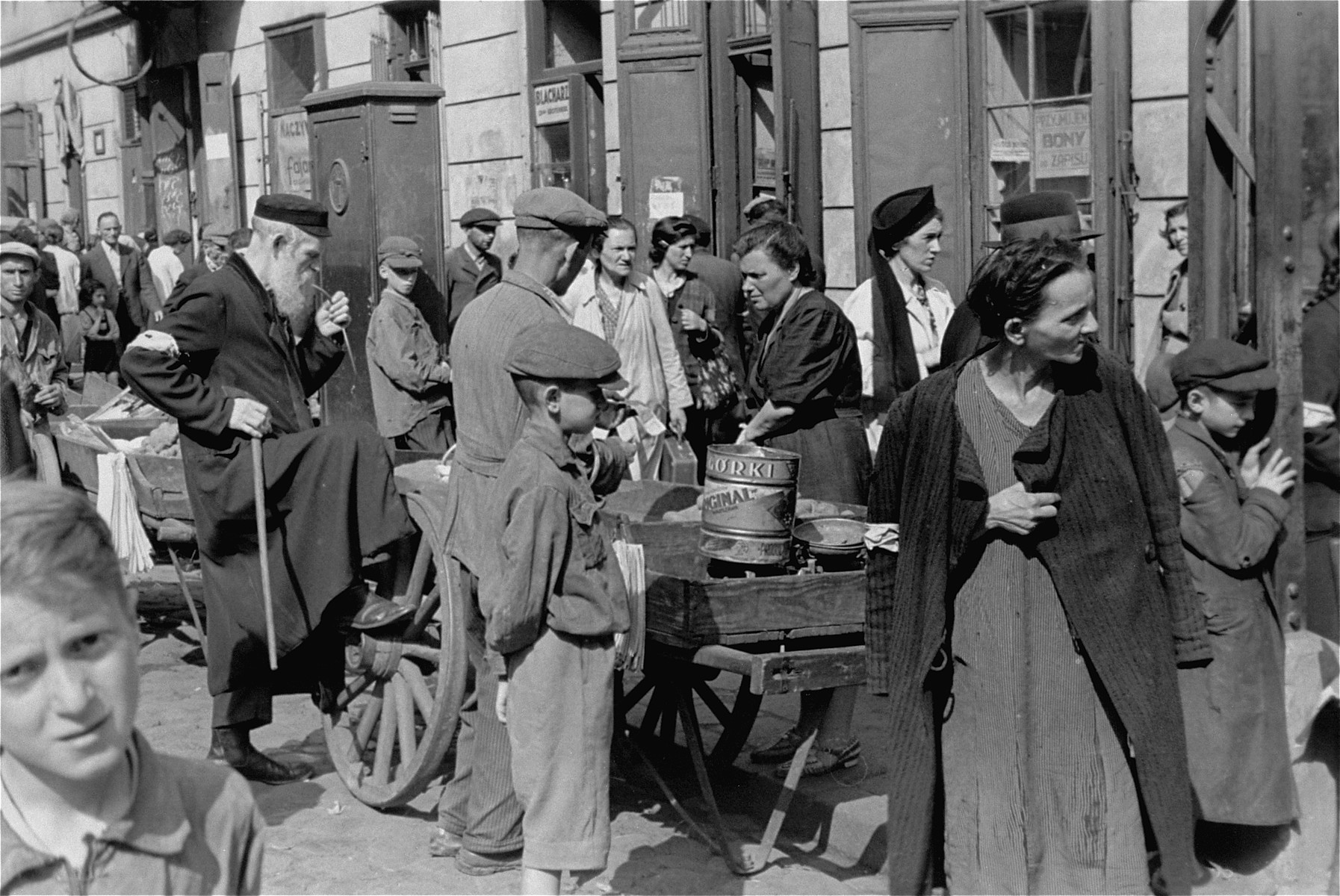 Vendors and buyers in an open air market in the Warsaw ghetto.