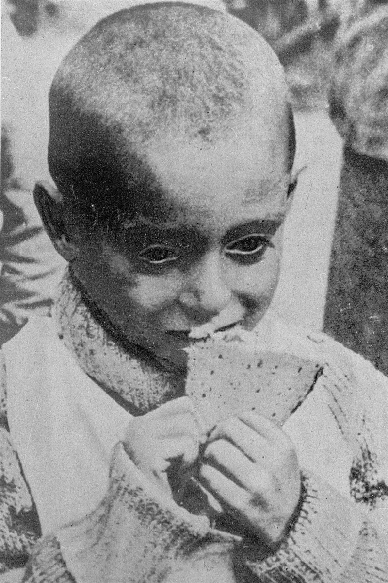 Portrait of a starving child eating a piece of bread in a hospital in the Warsaw ghetto.