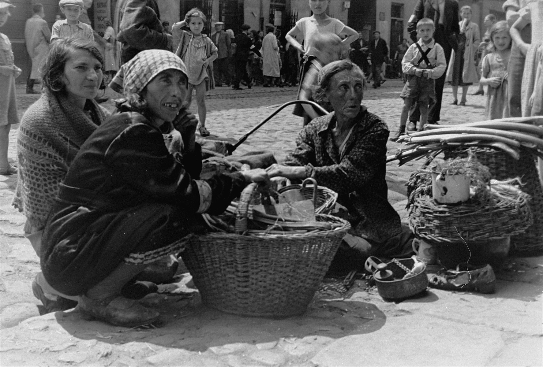 Three women sell household items on the street in the Warsaw ghetto.