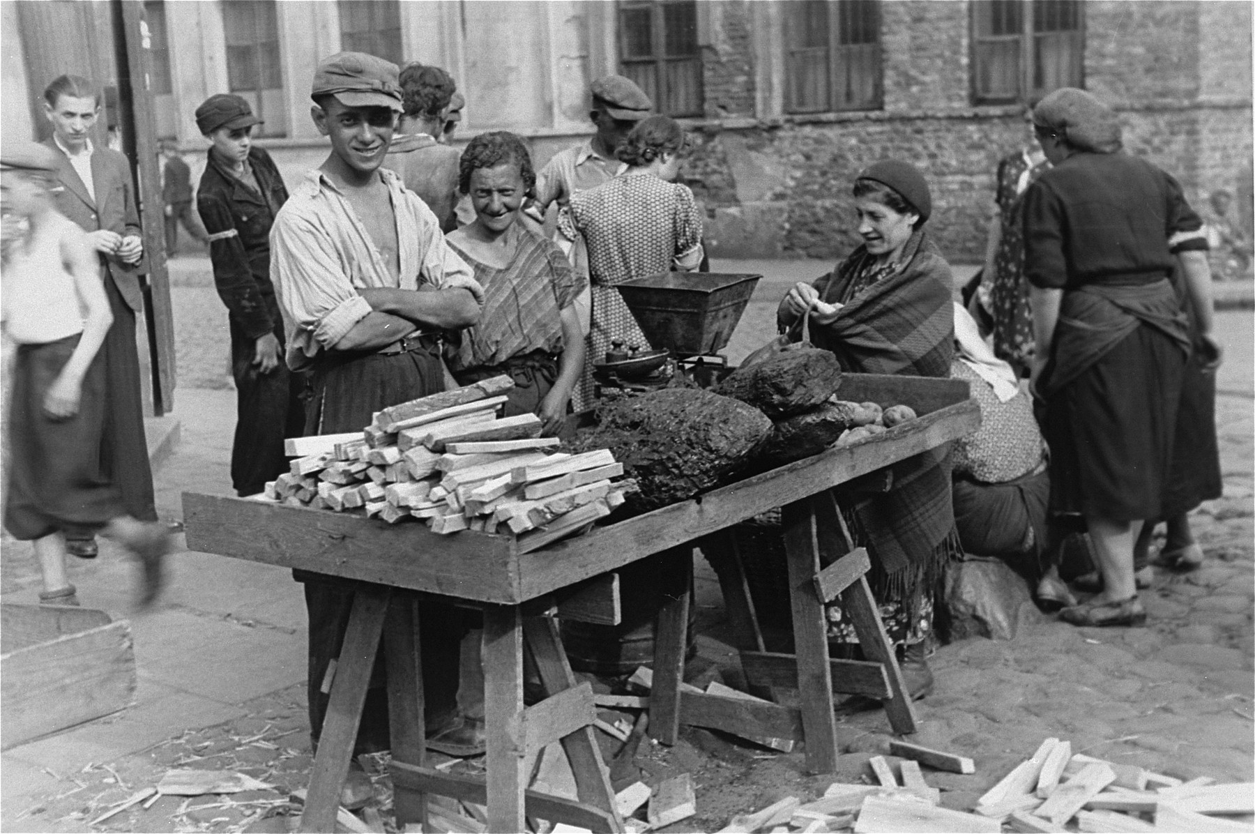 A street vendor in the Warsaw ghetto selling coal and kindling.