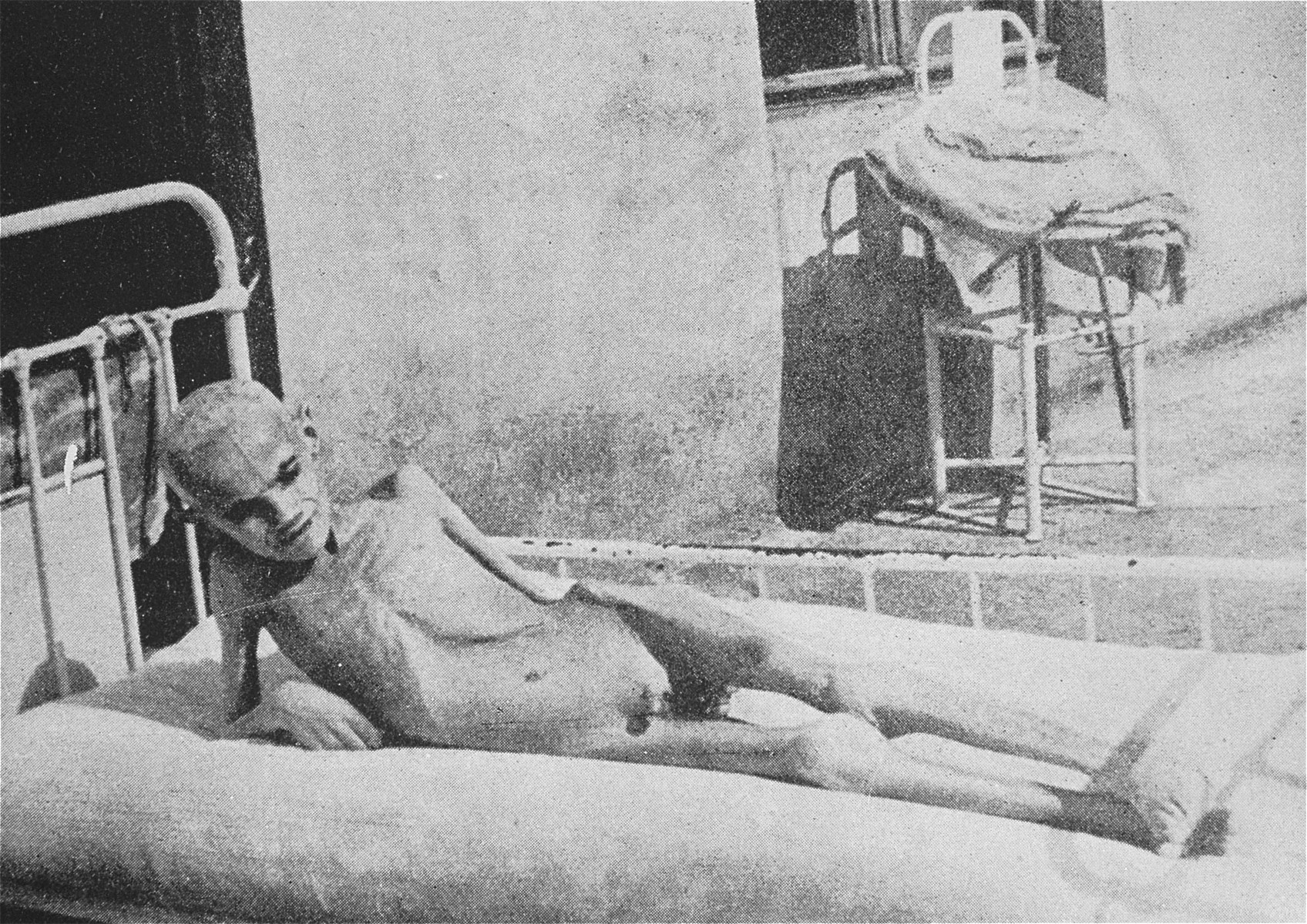 A starving child lies in a bed in a hospital in the Warsaw ghetto.
