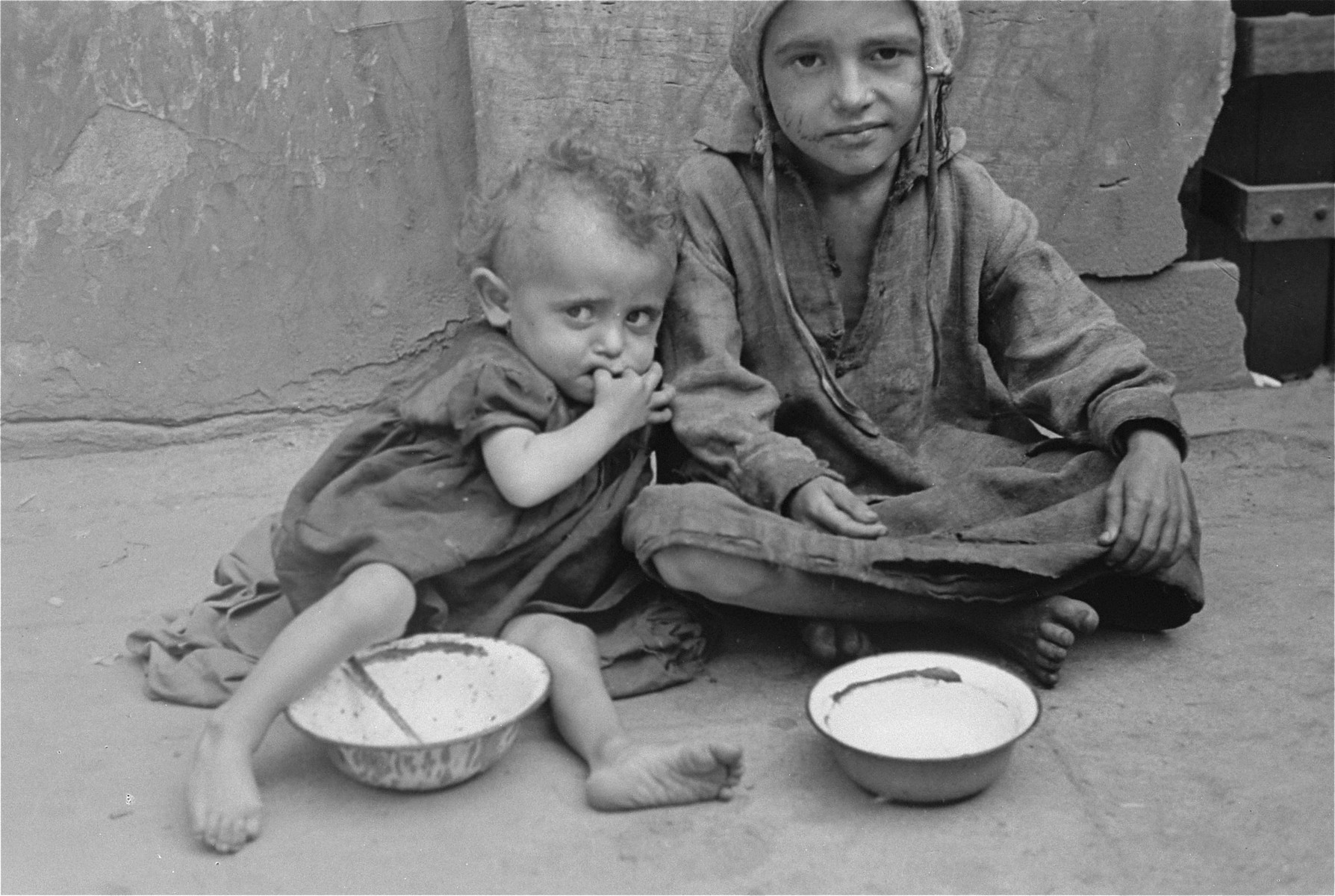 Two destitute children sit with empty bowls on a street in the Warsaw ghetto.