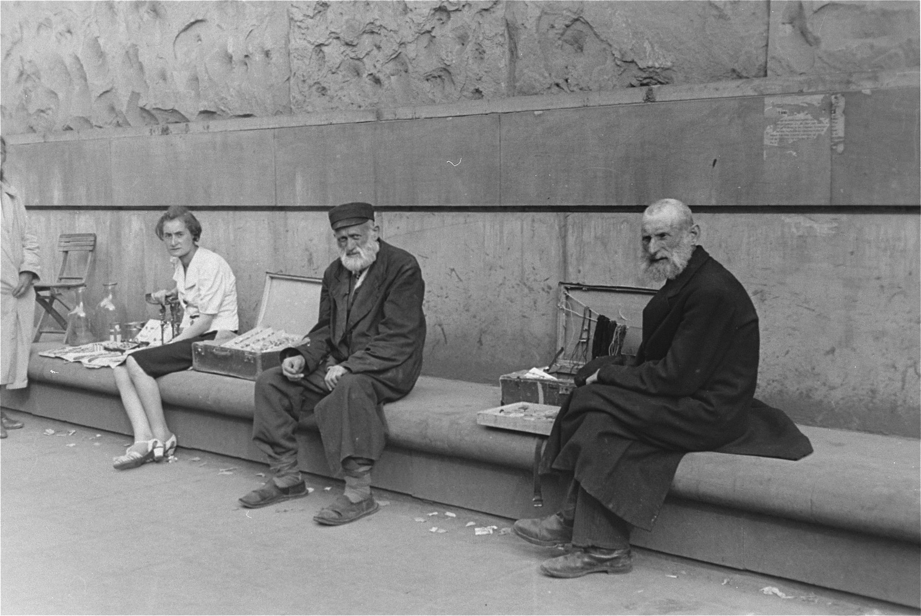 Three street vendors who are seated on a long bench, display their wares in the Warsaw ghetto.
