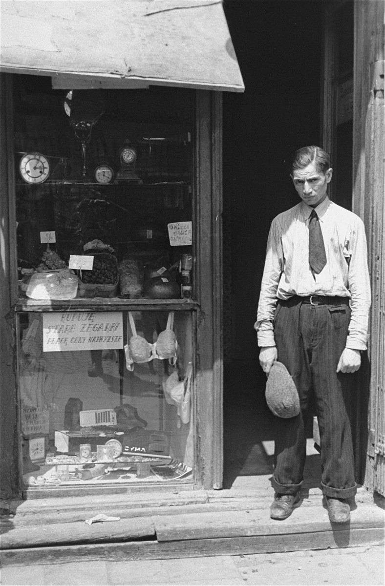 "A young man stands in the doorway of a shop in the Warsaw ghetto.  He has taken off his hat in compliance with the German regulation that Jews remove their hats in the presence of German personnel.  The sign in the window reads: ""Buying old watches, will pay top prices."""
